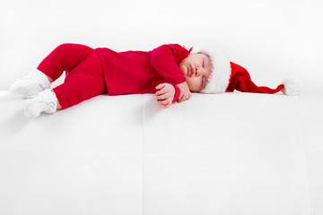 Cute baby in Santa hat sleeping in Christmas night
