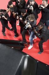 Paparazzi taking photos of celebrity's car