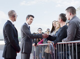Politician shaking hands with people behind barrier