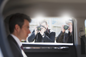 Paparazzi taking pictures of politician in car