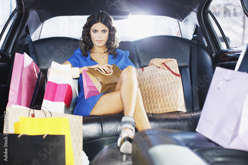 Woman with shopping bags in limo