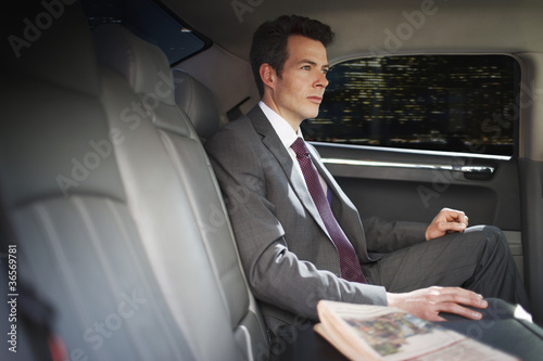 Politician sitting in backseat of car