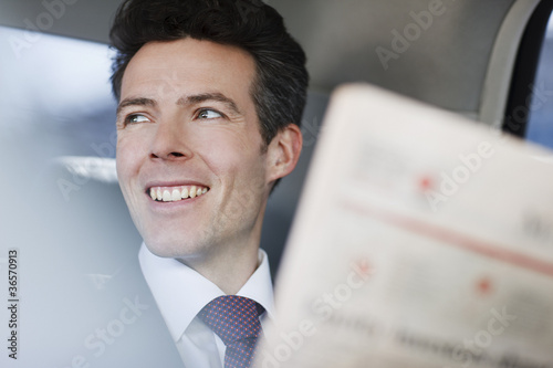 Businessman reading newspaper in backseat of car