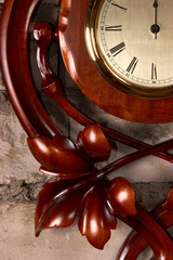 element of antique carved wooden clock on brick wall