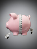 Measuring tape wrapped around piggy bank