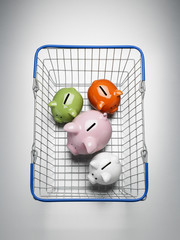 Piggy banks in shopping basket