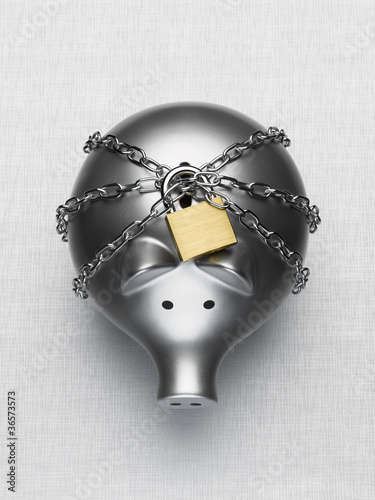 Padlock and chain around piggy bank