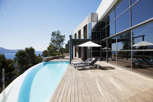Lounge chairs and pool outside modern house