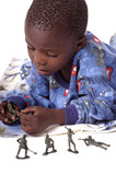A sick little boy playing with army men