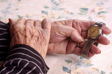 Elderly women holding her watch