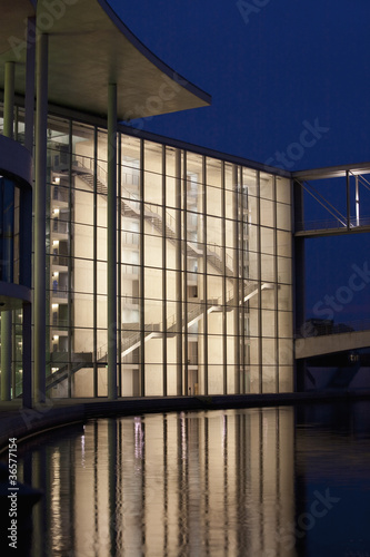 Modern building on water lit up at night