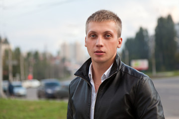 Portrait of a handsome man in a black jacket. Blond hair