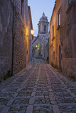 Cobbled alleyway of old city lit up at night