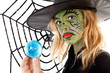 green Halloween witch girl in closeup holding big blue marble