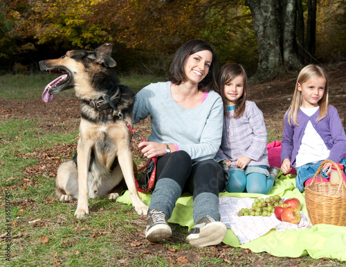 Mother with two daughters and a dog on picnic in forest