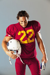 Football player carrying helmet