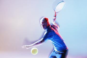 Tennis player swinging racket