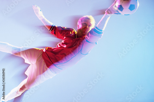 Blurred view of soccer player lunging for ball