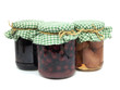 pickled pear,  plum jam and preserved cherries in glass jars