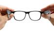Leinwanddruck Bild - Human hands holding retro style eyeglasses