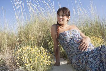 Pregnant woman sitting on beach