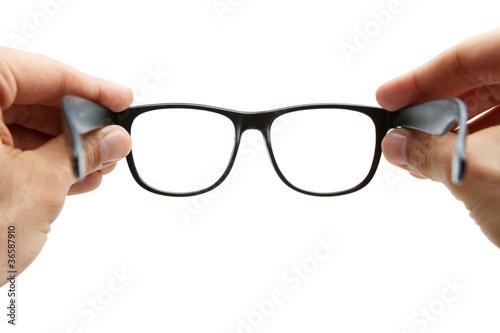 Leinwanddruck Bild Human hands holding retro style eyeglasses