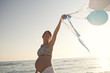 Pregnant woman carrying balloons on beach