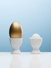 Large golden egg with small white egg