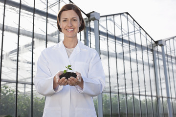 Scientist holding seedling outside greenhouse