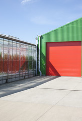 Greenhouse and warehouse under blue sky