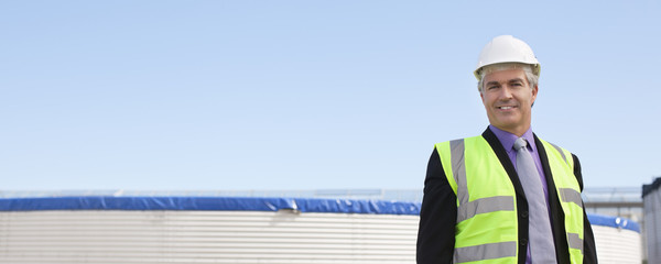 Businessman in safety gear standing outdoors