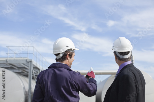 Worker and businessman examining tanks outdoors