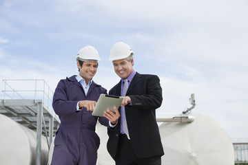 Businessman and worker using tablet computer outdoors