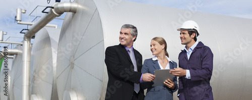 Business people using tablet computer by tanks