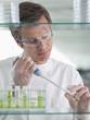 Scientist putting liquid in test tube in lab