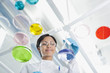Scientist examining petri dishes and beakers in lab