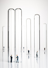Business figurines placed in and around test tubes