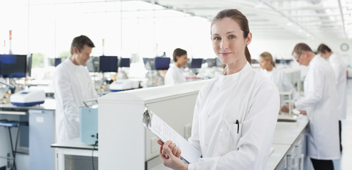 Scientist holding clipboard in lab