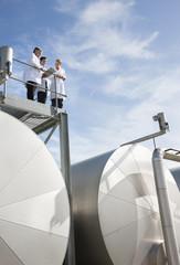 Scientists standing on walkway on tanks
