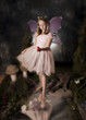 little girl dressed as fairy holding red bird