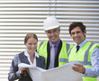 Business people examining blueprints on site