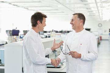 Scientists shaking hands in lab