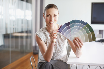 Businesswoman with paint swatches in office