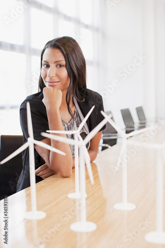 Businesswoman with wind turbine models in office