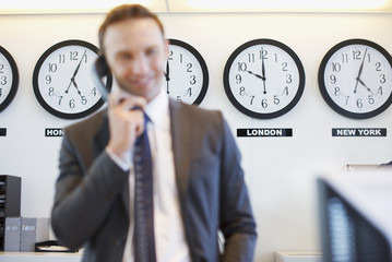 World clocks behind businessman in office