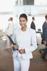 Businesswoman carrying folders in office