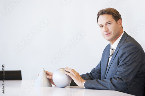Businessman at desk with sculptures