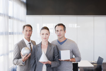 Business people holding sculptures in office