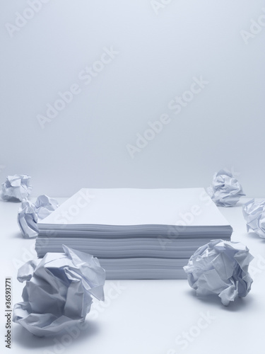 Crumpled balls of paper with stack of paper