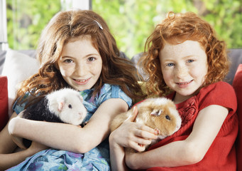 Girls holding pet hamsters in living room